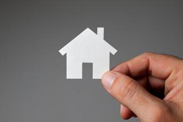 Hand holding model house.