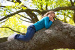 Children kid girl resting lying on a tree branch
