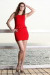 young woman in red dress on the pier
