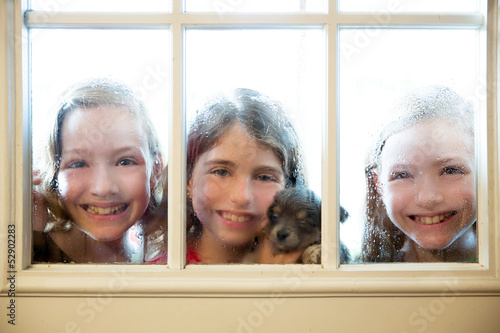 three sister friends looking through the rainy window
