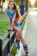 roller girl wearing jeans sitting on iron fence