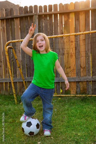 Blond little girl soccer player happy in backyard