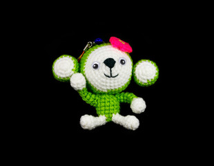 handmade crochet monkey doll on black background