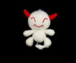 handmade crochet white devil with red ear doll on black backgrou