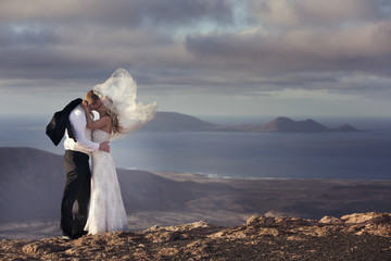 Bride and groom kissing on the volcanic landscape background.