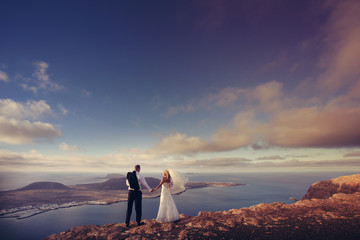 Newlyweds staring at the horizon in Canary Islands.