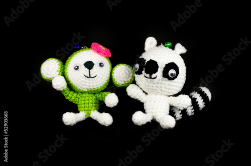 handmade crochet monkey and Raccoon doll on black background