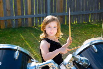 Drummer blond kid girl playing drums in tha backyard