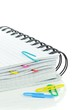 A spiral notebook and coloured paperclips on white background