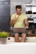 Young man using laptop on kitchen counter