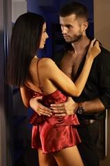 Sexy couple embracing in bedroom door