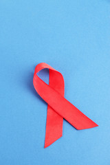 Red ribbon HIV, AIDS on blue background