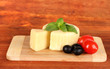 Cheese mozzarella,basil and vegetables on wooden background