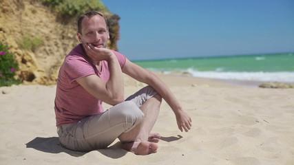 Young cheerful man sitting on beautiful beach