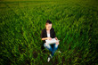 puzzled woman in a green field with a laptop. summer