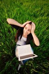 woman in a green field with a laptop. summer