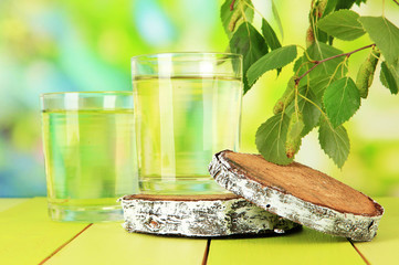 Glasses of birch sap on wooden table, on green background