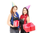Two female friends standing close together and holding gifts at