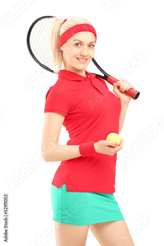Smiling female holding a tennis racket and a ball