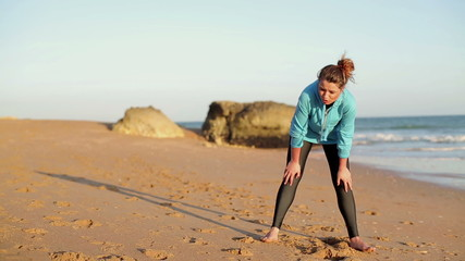 Tired woman catching breath during jogging on the beach