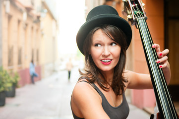 Woman in hat playing double bass on the street