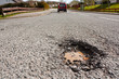 Pot hole in residential road surface - 52913658
