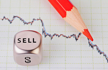 Downtrend chart,red pencil and dice cube with the word SELL. Sel