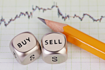 Dices cubes with the words SELL BUY, pencil and financial chart