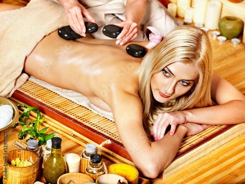 Woman getting stone therapy massage .