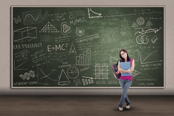 Asian female student standing at written board