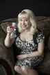 Beautiful Young Woman with Blond Hair Drinking a Pink Martini