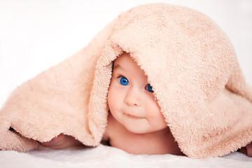 baby girl is hiding under the beige terry towel