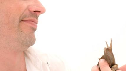 Man kissing snail. Close-up