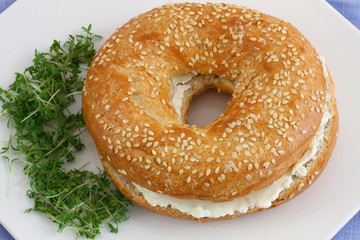 Bagel with cream cheese with watercress garnish