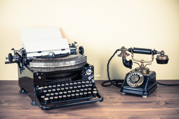 Vintage telephone, old typewriter on table