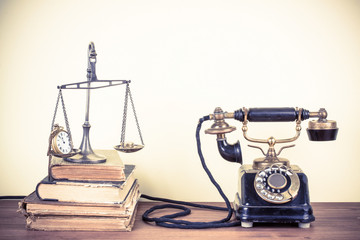 Vintage old telephone, scales with watches and money, books