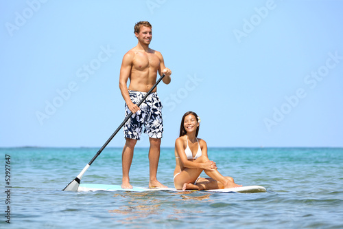 Beach fun couple on stand up paddleboard