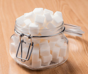 glass jar full of white sugar cubes on wooden base