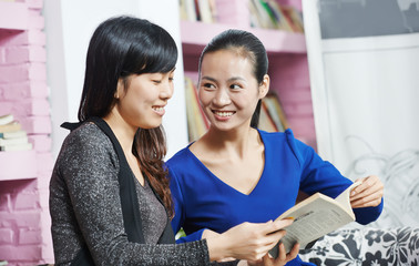 young chinese girls with book in library