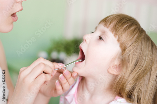 Pediatrician examining little girl's throat
