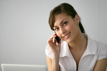 Brunette with laptop making telephone call