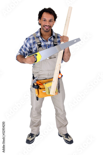 Worker holding a saw and a piece of wood