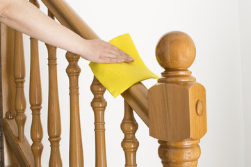 cleaning wooden railing with yellow cloth