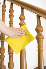 cleaning wooden railing with yellow cloth vertical