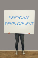 Woman holding personal development sign