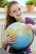 Schülerin zeigt auf Globus