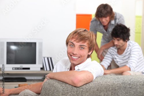 Three young men about to watch television