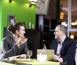 Two men in suits at restaurant cheerfully talk