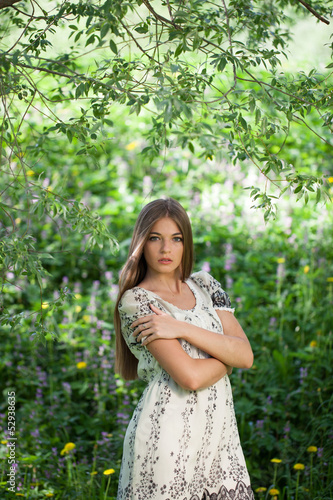 Beautiful girl among the meadow flowers
