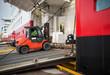 Lift truck unloads big passenger ship through opened side ramp